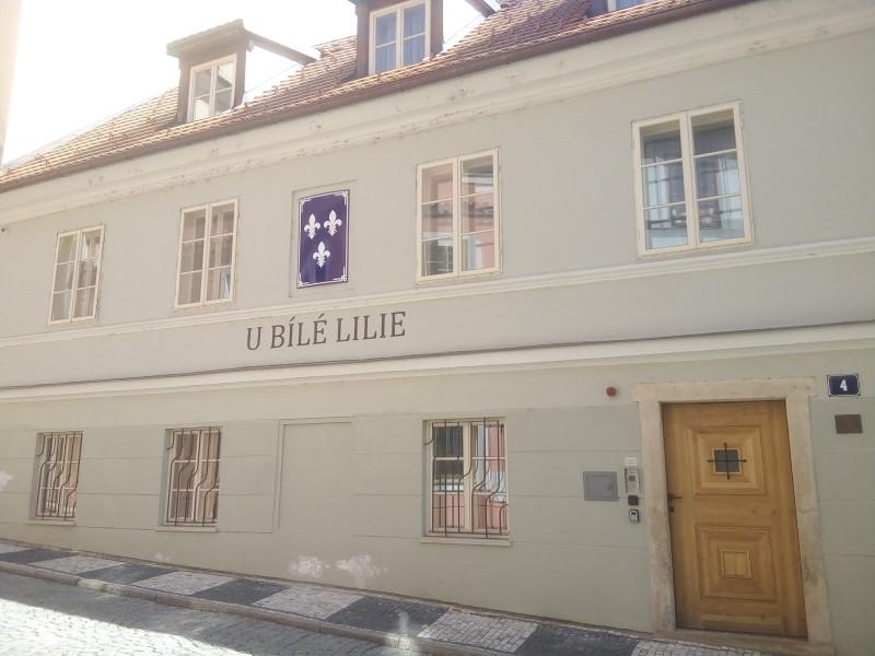 Facciata dell'albergo u Bílé Lilie con lo stemma dei tre gigli bianchi in campo blu.